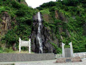 国道開通の碑の奥に落ちる白銀の滝